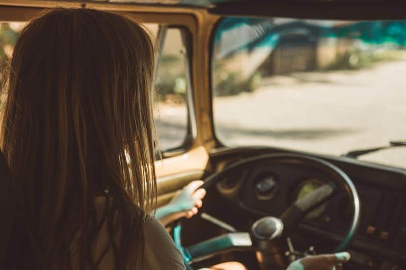 Girl behind the wheel on a road tr